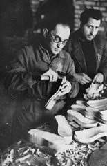 Jewish forced laborers at work making shoes in a ghetto...