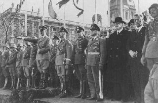 Adolf Hitler and entourage view a military parade following...