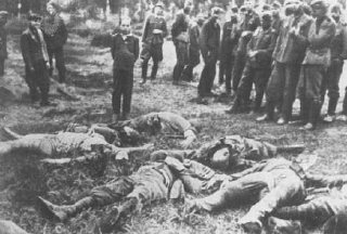 Members of an Einsatzkommando (mobile killing squad) before shooting a Jewish youth. The boy's murdered family lies in front of him; the men to the left are ethnic Germans aiding the squad. Slarow, Soviet Union, July 4, 1941.