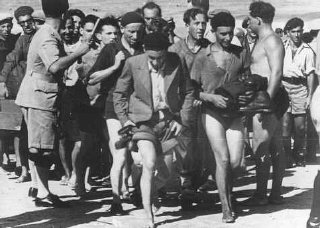 "A British policeman (left) organizes the arrest of passengers from the Aliyah Bet (""illegal"" immigration) ship ""Parita"" after th"