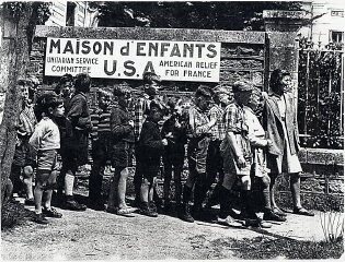 French children wait in line to receive assistance...