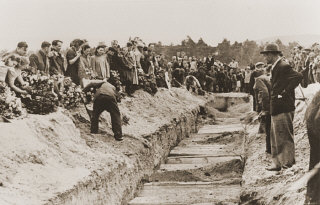 Mourners and local residents shovel dirt into the mass...