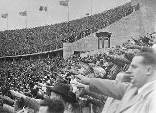 In the Olympic Stadium, German spectators salute Adolf...