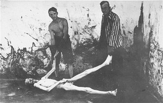 Survivors of the Dachau concentration camp prepare to move a corpse during a demonstration of the cremation process at the camp. Dachau, Germany, April 29-May 10, 1945.
