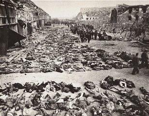 German civilians remove the bodies of prisoners killed...