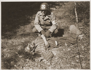 An American soldier kneels by the corpse of a prisoner on the roadside near Gardelegen.