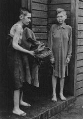 Deux survivants en face des baraques des femmes dans...