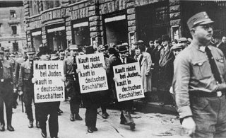 "Three Jewish businessmen are forced to march down a crowded Leipzig street while carrying signs reading: ""Don't buy from Jews."
