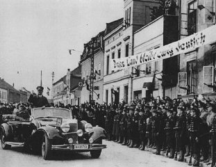 "Hitler enters Memel following the German annexation of Memel from Lithuania. The banner states that ""This land will remain forever German."" Memel, March 1939."