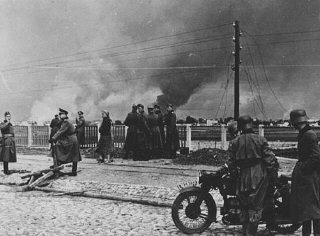 German forces in the outskirts of Warsaw. In the background of the photograph, the city burns as a result of the German military assault. Warsaw, Poland, September 1939.