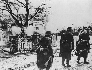 German troops pass through a village during the invasion...