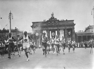 On August 1, 1936, Hitler opened the 11th Summer Olympic Games. Inaugurating a new Olympic ritual, a lone runner arrived bearing a torch carried by relay from the site of the ancient Games in Olympia, Greece. This photograph shows an Olympic torch bearer running through Berlin, passing by the Brandenburg Gate, shortly before the opening ceremony. Berlin, Germany, July-August 1936.