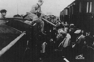 Jews from the Lodz ghetto are forced to transfer to a narrow-gauge railroad at Kolo during deportation to the Chelmno extermination camp. Kolo, Poland, probably 1942.