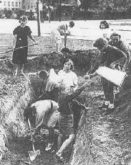 Men, women, and children dig defense ditches during...