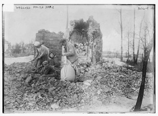 A man, women and a child sort through the rubble of...