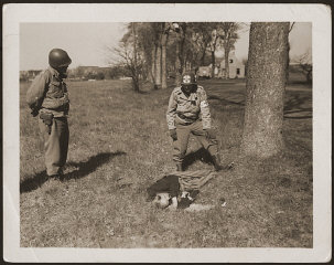 An American medic and soldier stand by the corpse of a prisoner shot on the road near Gardelegen.