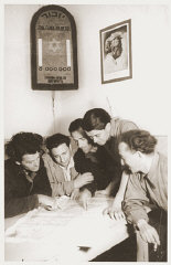 Members of Kibbutz Nili (a Zionist agricultural collective) study a map of Palestine.