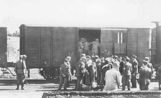 SS personnel stand guard while Lodz ghetto police board Jews onto a deportation train bound for Chelmno or Auschwitz.