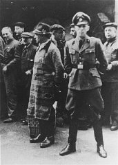 An SS officer stands in front of Jews assembled for...
