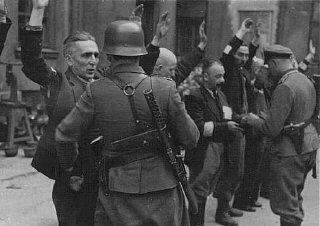 German soldiers arrest Jews during the Warsaw ghetto uprising.