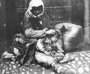 An Armenian woman and her child sit on a sidewalk next...