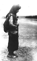 An Armenian refugee, wearing a scarf and a pack on...