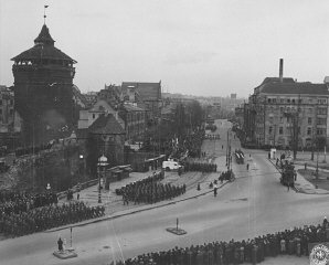 The inhabitants of Nuremberg watch a parade of US troops...