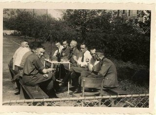 Karl Höcker (on left, looking at the camera) relaxes with SS physicians, including Dr. Fritz Klein (far left), Dr. Horst Schumann (partially obscured next to Klein, identified from other photographs), and Dr. Eduard Wirths (third from right, wearing tie).