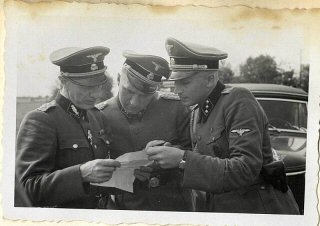 Richard Baer and Karl Höcker look over a document with SS-Standartenführer Dr. Enno Lolling, the director of the Office for Sanitation and Hygiene in the Inspectorate of Concentration Camps. From left to right: Lolling, Baer, Höcker.