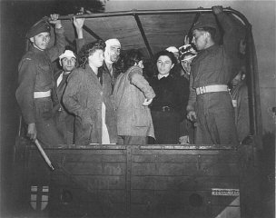 "British soldiers guard Jewish refugees, forcibly removed from the ship ""Exodus 1947,"" on trucks leaving for Poppendorf displaced persons camp. Photograph taken by Henry Ries. Kuecknitz, Germany, September 8, 1947."
