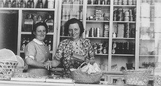 Two German Jewish refugee women stand behind the counter...