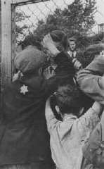Jewish children say goodbye to parents through the fence of the Central Prison, the assembly point for deportations.