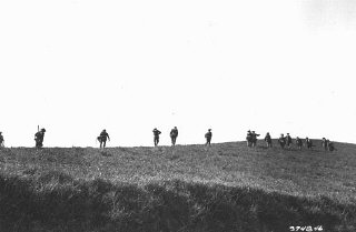 Members of the Jewish Brigade Group move to take up...