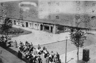 Jews carry luggage to an assembly point before deportation...