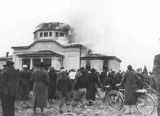 "Local residents watch  the burning of the ceremonial hall at the Jewish cemetery in Graz during Kristallnacht (the ""Night of Broken Glass""). Graz, Austria, November 9-10, 1938."