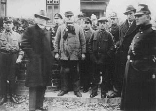Jews arrested during Kristallnacht stand under guard...