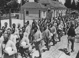 Prisoners carrying bowls in the Dachau concentration camp.