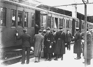 Jewish deportees, guarded by French police, board a train at the Austerlitz station for transport to the Pithiviers internment c