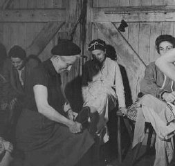 Soon after liberation, a British woman helps a camp survivor try on shoes.