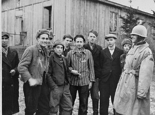 A US army officer (far right) poses with survivors...