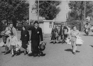 Jews proceed to an assembly point before deportation...