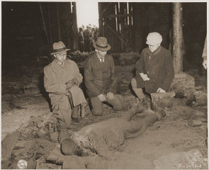 Three German mayors view the corpse of a prisoner burned...