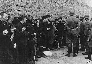 German soldiers interrogate Jews captured during the Warsaw ghetto uprising.