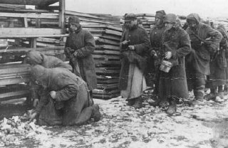Soviet prisoners of war pause for rations during forced...