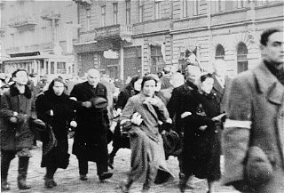 Jews from the Warsaw ghetto are marched through the ghetto during deportation. Warsaw, Poland, 1942-1943.