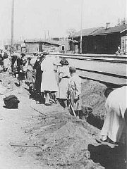 Jewish women deported from Bremen, Germany, are forced to dig a trench at the train station.