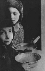 In the Warsaw ghetto, Jewish children with bowls of soup.