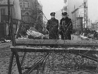 Jewish police at a barricaded entrance to the Warsaw...