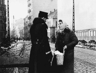 A Polish policeman searches the bag of a Jewish resident...