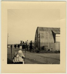 A young baby sits in its carriage next to a Quonset...